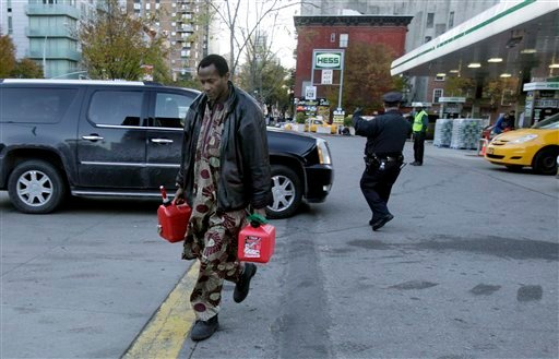 A man carries two filled gas cans at a gasoline station in New York on Friday. Gas is available to drivers with license-plate numbers ending in an odd number or a letter on Friday. On Saturday, drivers with license plates that end in even numbers or zero can fuel up.