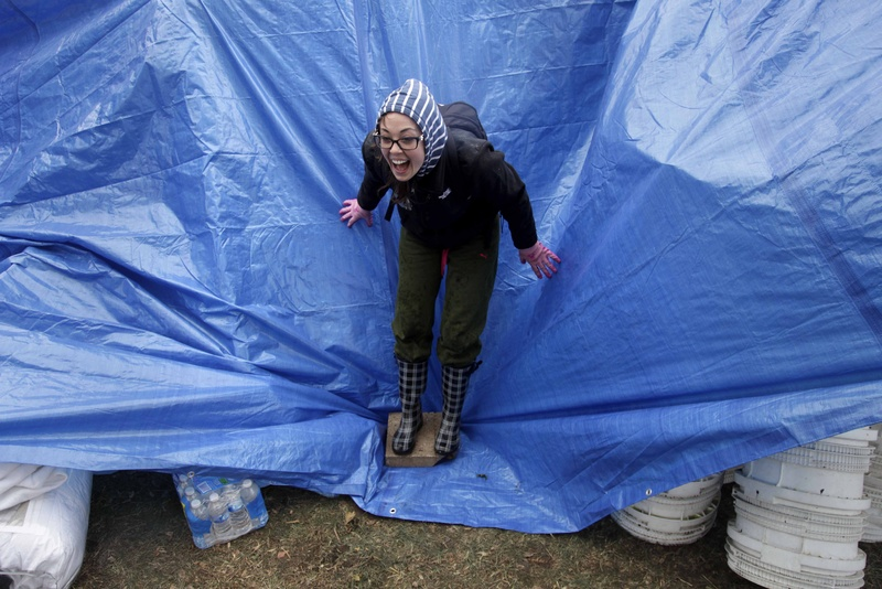 Gina Kohm reacts as a gust of wind almost rips a tarp off of a pile of donated supplies at an aid station on Staten Island, New York on Wednesday. Residents of New York and New Jersey who were flooded out by superstorm Sandy are waiting with dread Wednesday for the second time in two weeks as another, weaker storm heads toward them.