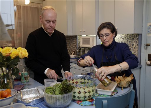 """Karen Nelson, and her house guest Gregory Downer prepare dinner in her upper west side apartment in New York on Thursday evenin. Like herself, her neighbors have taken in dozens of """"refugees,"""" people who have fled their cold, dark homes in search of a roof, food, a hot shower and juice for their cell phones, iPads and laptops."""