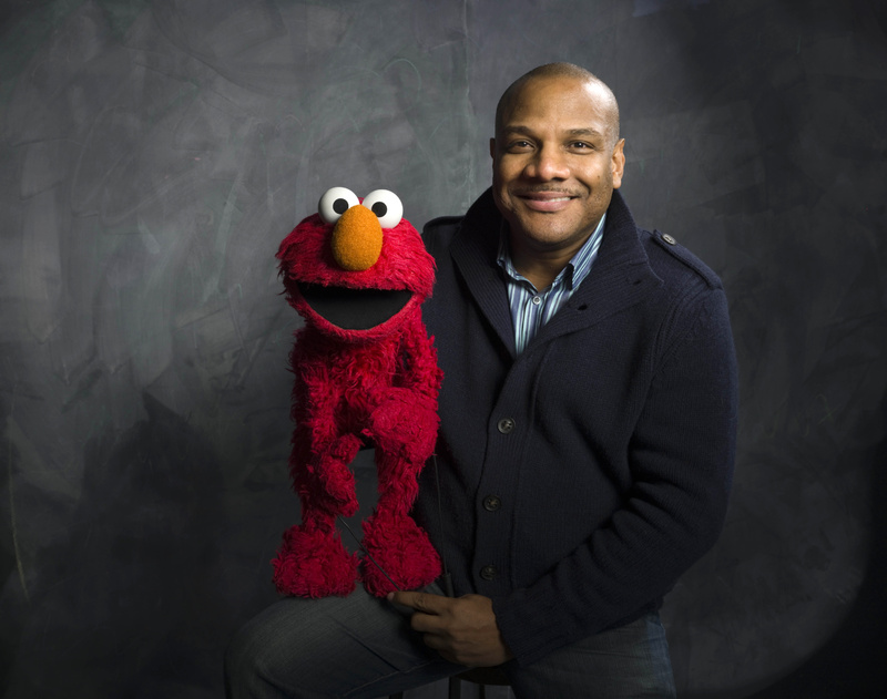 """Kevin Clash poses for a portrait with """"Sesame Street"""" muppet Elmo in 2011."""