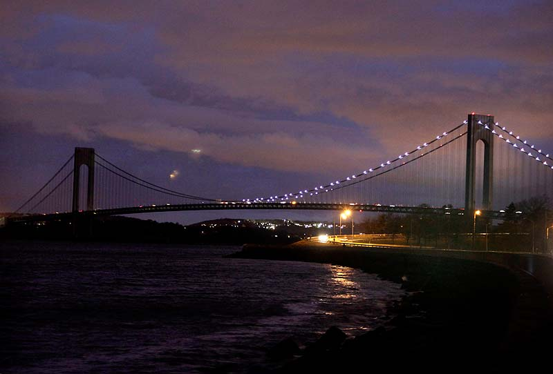 The half of the Verrazano Narrows Bridge attached to Brooklyn is lit while the half attached to Staten Island is dark in New York on Friday.