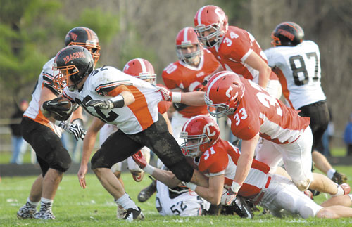 GET BACK HERE: Cony High School's Brandon St. Michel (31) and Reid Shostak (33) try to bring down Brunswick High School running back Jared Jensen in the first half of a Pine Tree Conference Class A seminfinal game Saturday in Augusta.