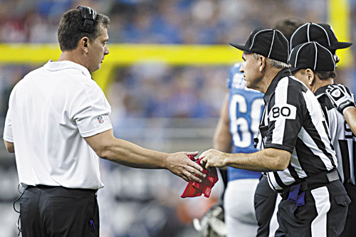 COSTLY ERROR: Field judge Greg Gautreaux (80) hands the red challenge flag back to Detroit Lions head coach Jim Schwartz after the coach mistakingly challenged a scoring play against the Houston Texans on Thursday in Detroit.