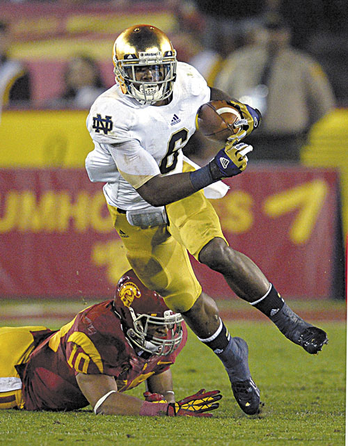 HERE I COME: Notre Dame running back Theo Riddick, left, runs the ball as Southern California linebacker Hayes Pullard tries to tackle him during the first half of the Fighting Irish's 22-13 win Saturday in Los Angeles.