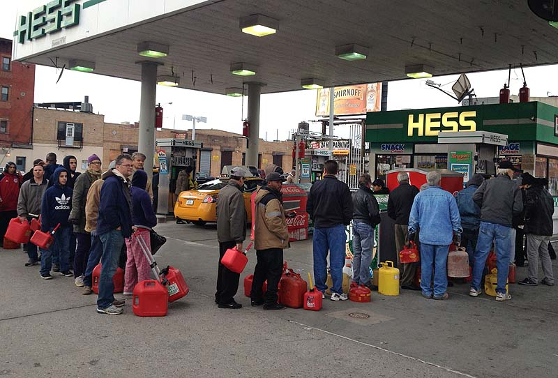 Shortly before the gas ran out, customers wait in line at a Hess station where the line of cars snaked 10 blocks, and at least 60 people waited to fill red gas cans for their generators, in the Gowanus section of Brooklyn.
