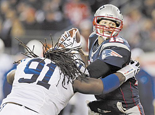 HERE IT COMES: New England Patriots quarterback Tom Brad, right, eludes Indianapolis Colts defensive end Ricardo Mathews (91) to get a pass off during the second quarter Sunday at Gillette Stadium in Foxborough, Mass.