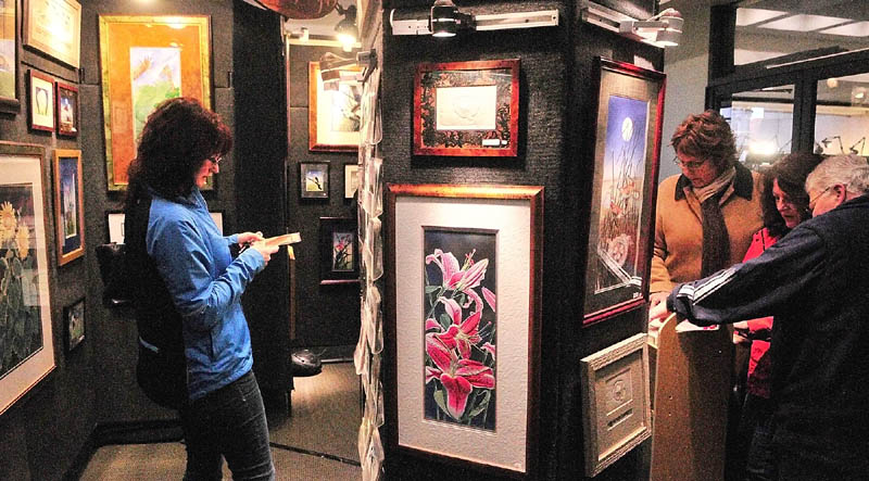 Show-goers look at the Island Designs booth on Saturday afternoon during 16th Annual Crafts at the Museum Show in Augusta. The Maine State Museum is located off of State Street just south of the State House and show continues today from 10 a.m.to 4 p.m.