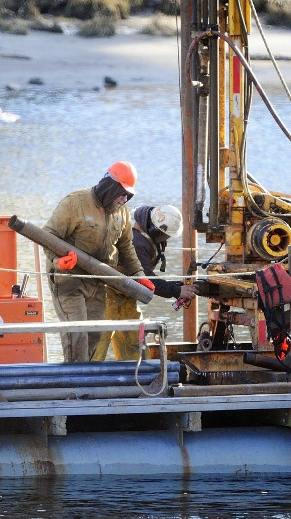 Workers drill from a barge on Thursday morning in the middle of the Kennebec River, in downtown Augusta.