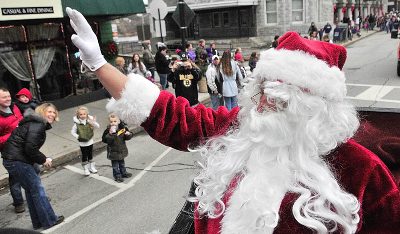 Santa Claus waves as he rides down Water Street in a horse-drawn carriage driven by Cathy Simmons, of S&S Carriage Rides, before the annual tree lighting events on Saturday, on Water Street in downtown Augusta.