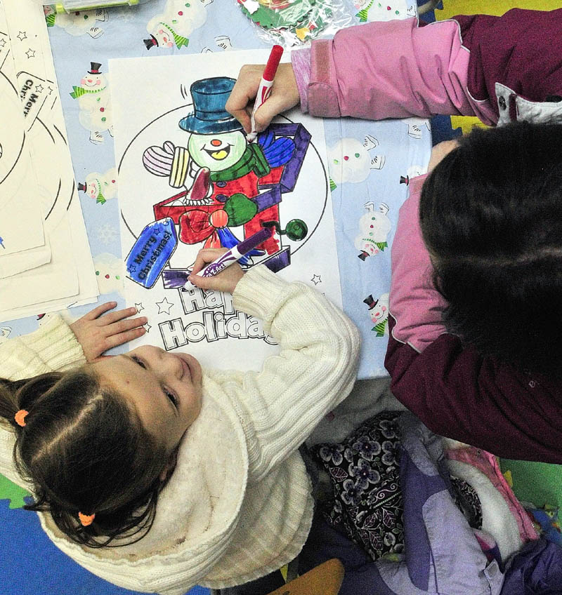 Jenna Jensen, 4, and her mother, Natasha Jensen, both of Portland, work on coloring a picture in a craft room that was part of the annual tree lighting events on Saturday, on Water Street in downtown Augusta.