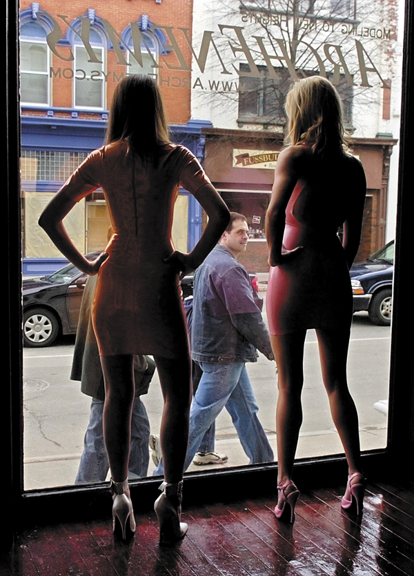 This April 2007 file photo shows passers-by watching live models Emily Owen, left, and Shayna Ferguson, in the window of the Archenemys shop on Water Street in downtown Augusta. augusta business lachance carrie nate religion