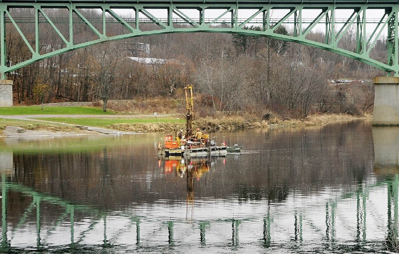 Workers drill from a barge on Tuesday afternoon in the middle of the Kennebec River, in downtown Augusta.