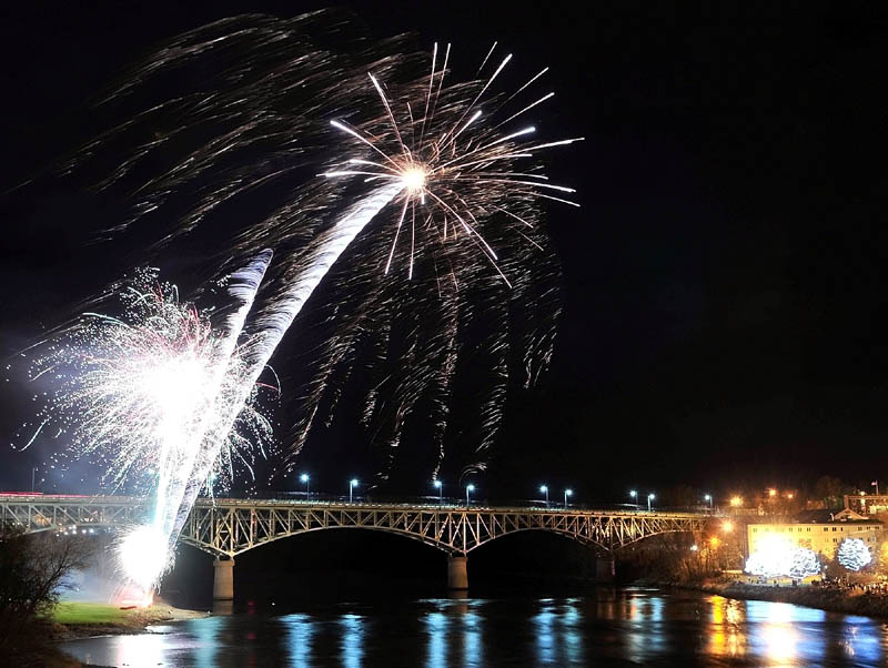 Fireworks are launched over the Kennebec River from the East Side Boat Landing, left, as spectators watch from beneath lighted trees in Waterfront Park, after the annual tree lighting ceremony in Augusta on Saturday.