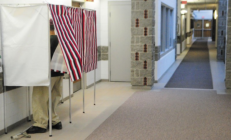 Mike Bradley fills in his absentee ballot in a voting booth in a hallway near the city clerk's office recently in Augusta City Center.