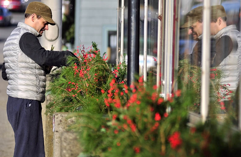 Neil Andersen decorates with berries and evergreens on Tuesday afternoon in the planter boxes on the front of the A1 Diner in Gardiner. Andersen said that it was the changing of the seasons and that he'd just taken down the pumpkins that had been lining the roof of the diner, built by the Worcester Dining Car Company in 1948, according to the diner's website.