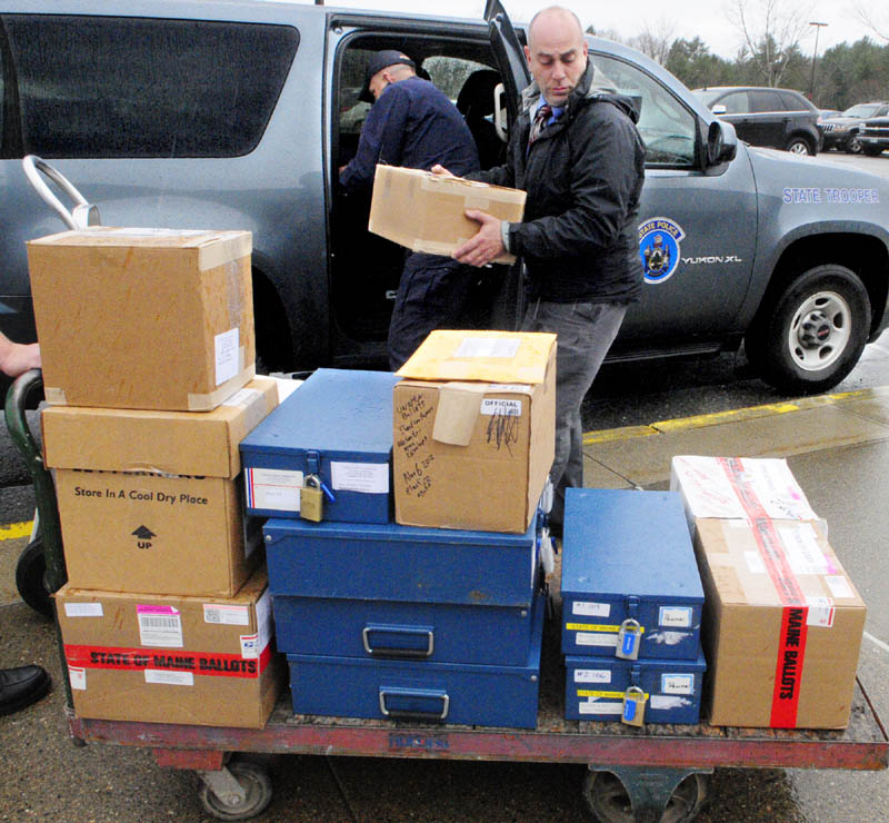 Maine State Police Trooper Jack Dow, left, reaches back into his vehicle for another ballot box as State Police Sgt. Mike Zabursky loads a cart on Tuesday afternoon, outside the Department of Public Safety headquarters on Commerce Drive in Augusta. Dow had collected ballot boxes in Gray, North Yarmouth and Pownal for recounts scheduled to begin Wednesday morning.