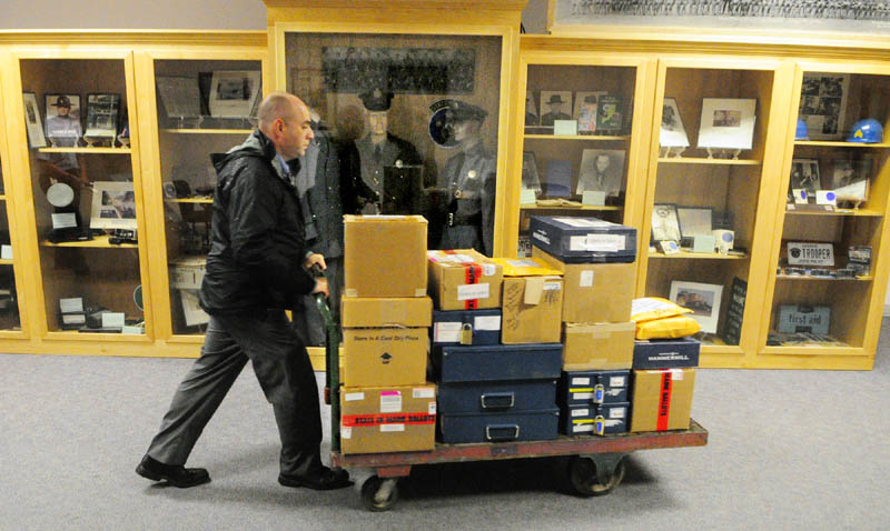 Maine State Police Sgt. Mike Zabursky rolls a cart of ballot boxes past display cases towards Florian Hall on Tuesday afternoon at the Department of Public Safety headquarters on Commerce Drive in Augusta. Troopers were bringing ballots boxes there for recounts scheduled to begin Wednesday morning.