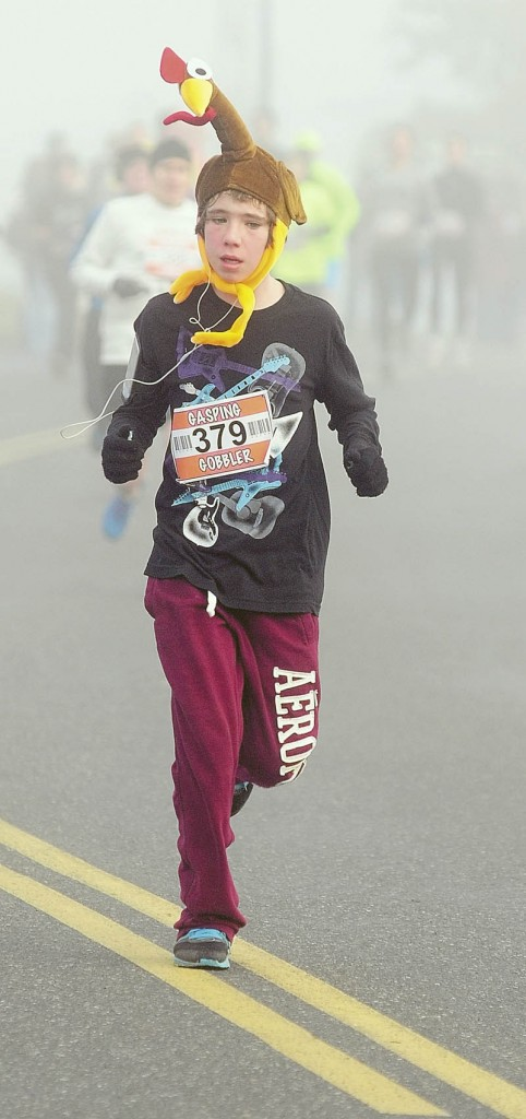 Evan West, of Manchester, wears a turkey while he runs in the Gasping Gobbler 5K race on Thursday morning that started and ended at Cony High School in Augusta. There were over 400 finishers in the annual Thanksgiving day race that gave food for prizes. The first male and female finisher got a trophy and full Thanksgiving dinner. In the each age group, the prizes were a turkey for first place, pie for second place and then dinner rolls for third.
