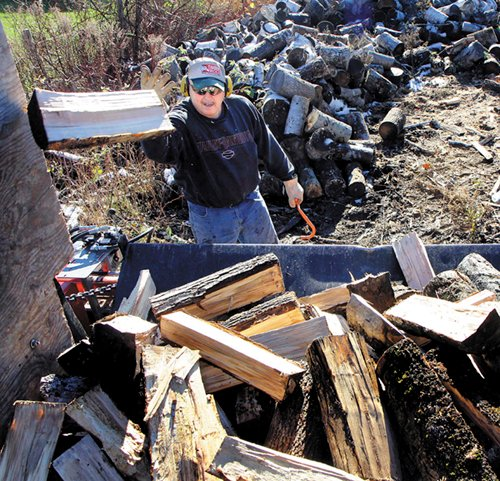 Bruce Lancaster loads a last-minute order of firewood for a customer near his home in North Vassalboro on Friday. Lancaster, who sells firewood as a second job, said he sold around 70 cords of wood so far this year.