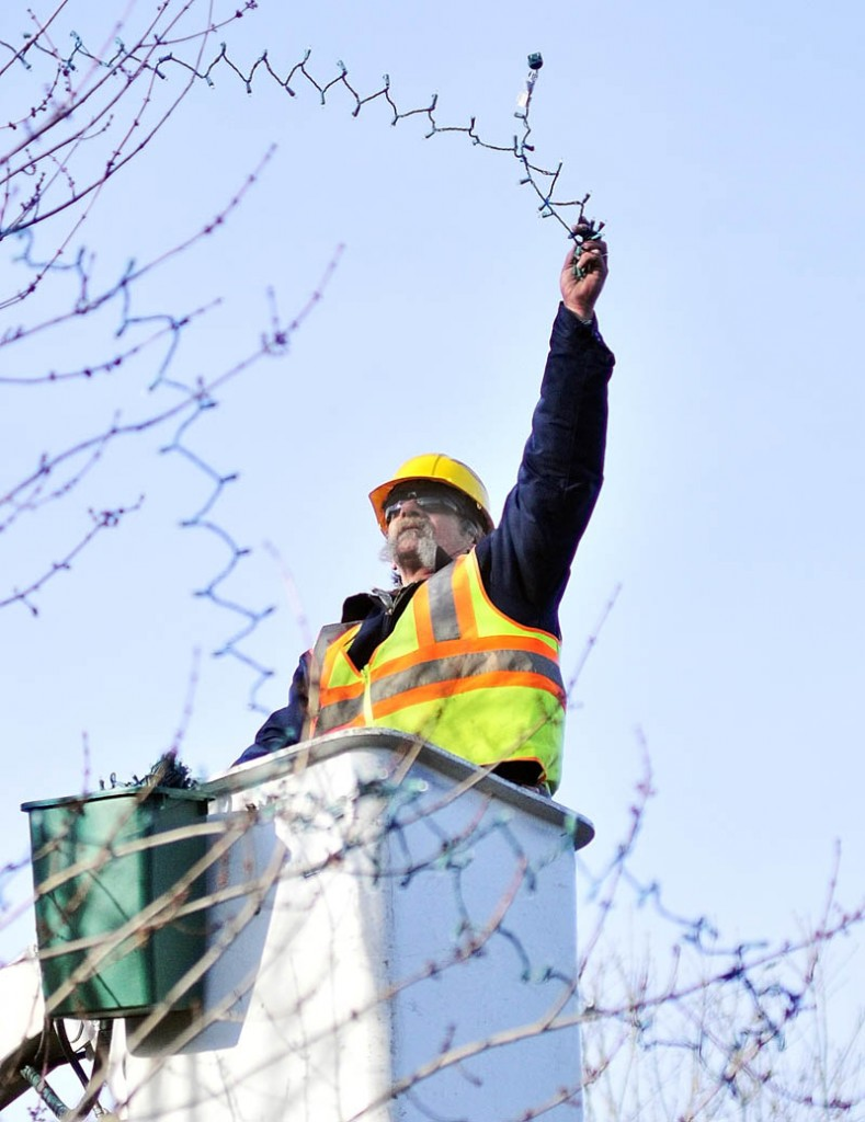 City worker Andy Chavarie strings holiday lights on a tree Thursday afternoon in Augusta Waterfront Park. Chavarie and and a coworker were putting almost 3,000 lights on several trees near the gazebo alongside the Kennebec River.