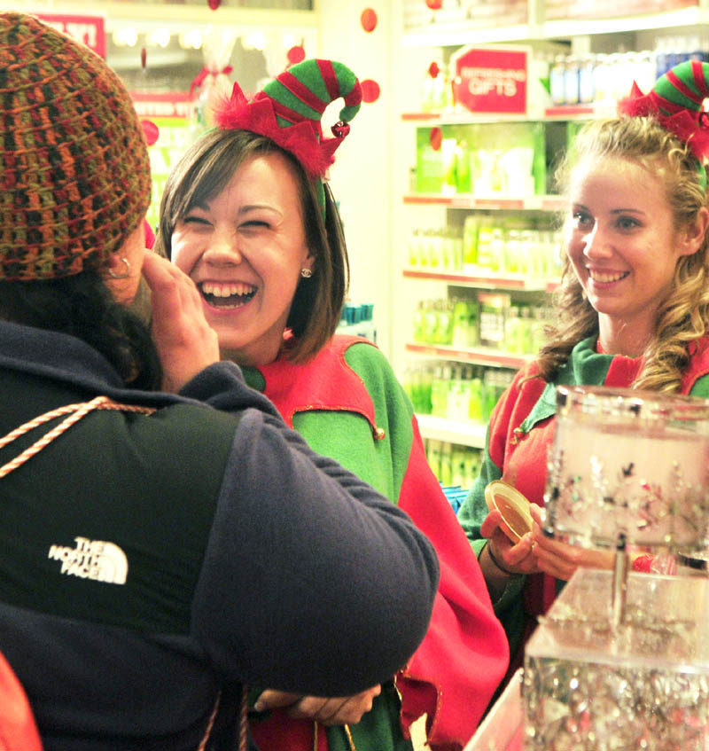 Customer Kari Turgeon, left, smells a candle as she is waited on by a pair of Bath & Body Works clerks dressed as elves at at 5:47 Friday morning in the Marketplace at Augusta. Alexis Saucier, center, said that she was Hermie the elf, while coworker Stephanie Smith's nametag read Buddy.