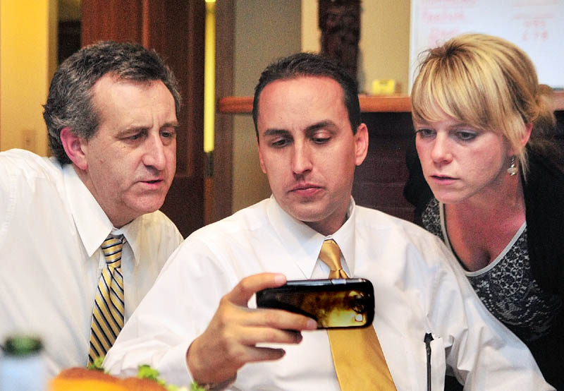 Staff photo by Joe Phelan Ron Bourget, district attorney candidate Darrick Banda, and Avian Moores look at results on Banda's phone on Tuesday night in Bourget's Augusta law office.