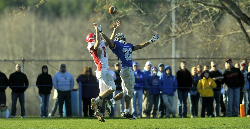 Cony High School's Chandler Shostack,left, and Lawrence High School's Xavier Lewis both make a play on a long Cony pass, but the fall fell incomplete Saturday.