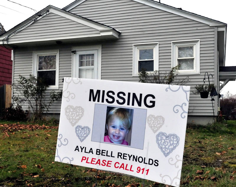 A sign and photograph of Ayla Reynolds has been placed in front of 29 Violette Ave. in Waterville, where she was reported missing nearly a year ago.