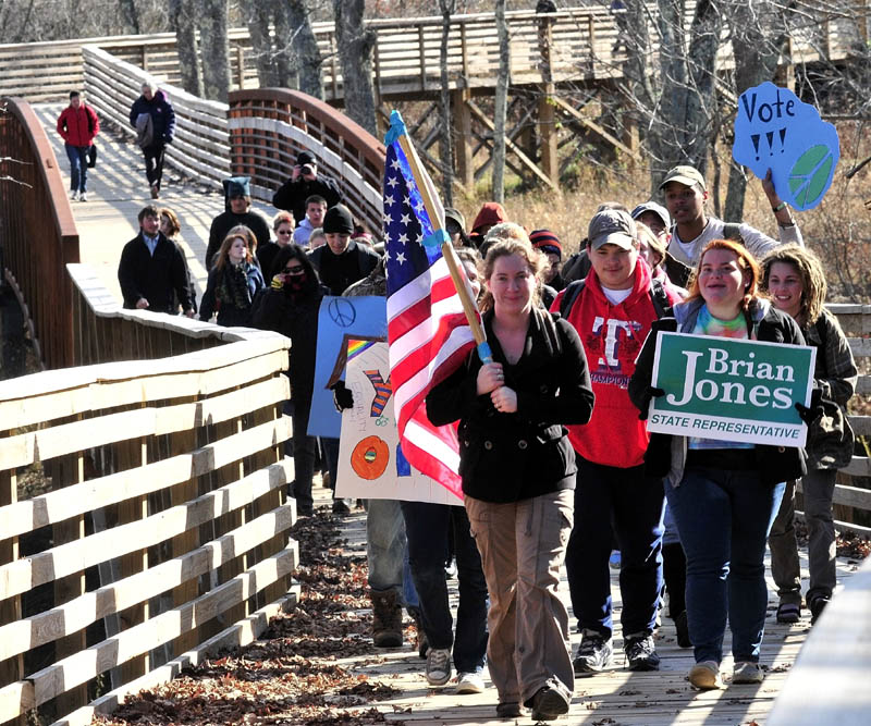 Unity College student Jena Zoller carries the American flag while leading 50 students and staff who marched along the CommUnity Trail from campus to town to vote on Tuesday.