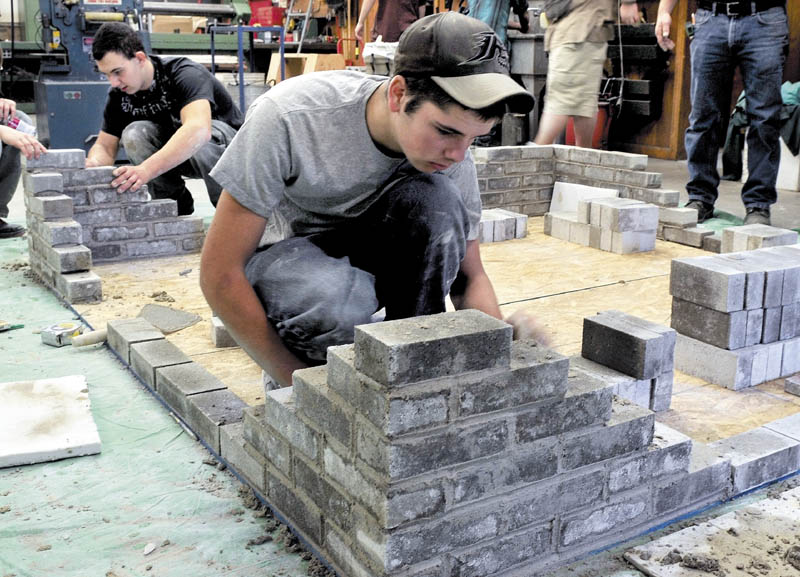 Carrabec High School industrial technology class students Ken White, left, and Francis Musotic build a brick structure on Wednesday. The students are learning skills that will be used when brick benches are made for the new front portico structure.