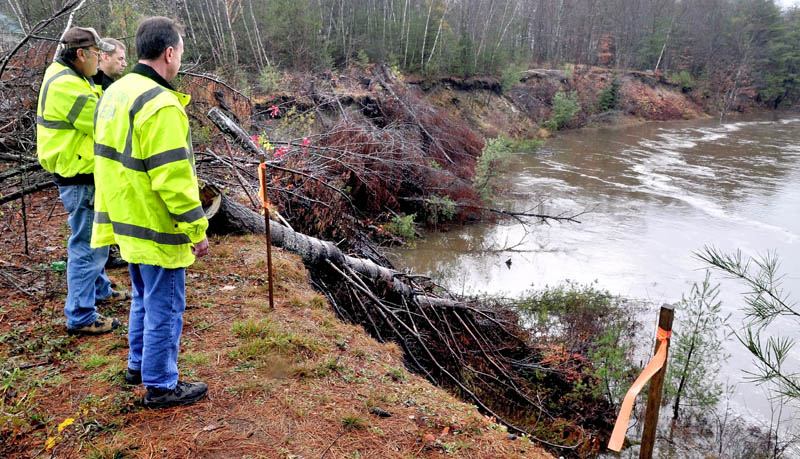 Farmington fire chief Terry Bell, in back, Public Works Director Denis Castonguay, left, and Franklin County Emergency Management Director Tim Hardy monitor the rising Sandy River in Farmington on Tuesday, at the site of erosion of a steep bank beside the Whittier Road.