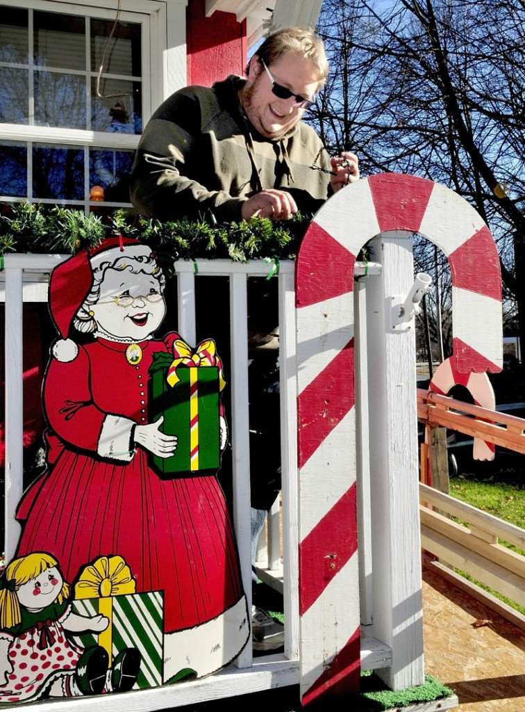 Alex Small, coordinator for the Parade of Lights, decorates Kringleville in Waterville on Sunday. The annual holiday season kickoff parade event is this Friday at 6 p.m., beginning at the American Legion and heading toward downtown Waterville.