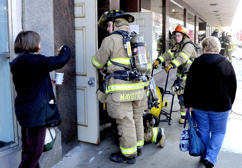 Maine Made & More shop employees Becky Turly, left, and Susan Begin, speak with Waterville firefighters, who were setting up fans to ventilate portions of The Center building, after a strange odor was detected on Monday. The building was evacuated and Main Street shut down for about two hours.