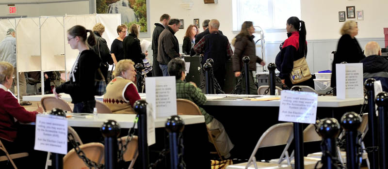 Waterville voters check in with ward clerks, in foreground, as others wait in line to cast their votes in machines at the busy American Legion Hall on Tuesday. There was concern earlier that a ballot counting machine had malfunctioned but was quickly restored, according to City Clerk Patty Dubois.