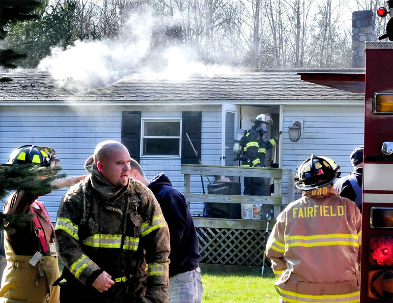 Smoke pours out through the roof of a mobile home badly damaged by fire on the Martin Stream Road in Fairfield on Monday, as firefighters change air tanks and enter the home.