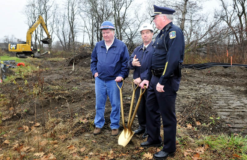 As workers remove trees in background, Waterville City Manager Michael Roy, center, motions to Police Chief Joseph Massey during a groundbreaking ceremony at the site of the new police department at Colby Circle on Tuesday. At left is City Councilor Fred Stubbert.