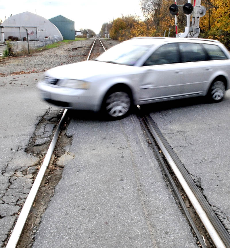 A driver goes over a bumpy Pan Am Railways crossing on Lawrence Avenue in Fairfield on Thursday. The town is working with the Maine Department of Transportation and the railroad to consider repairing the crossings.