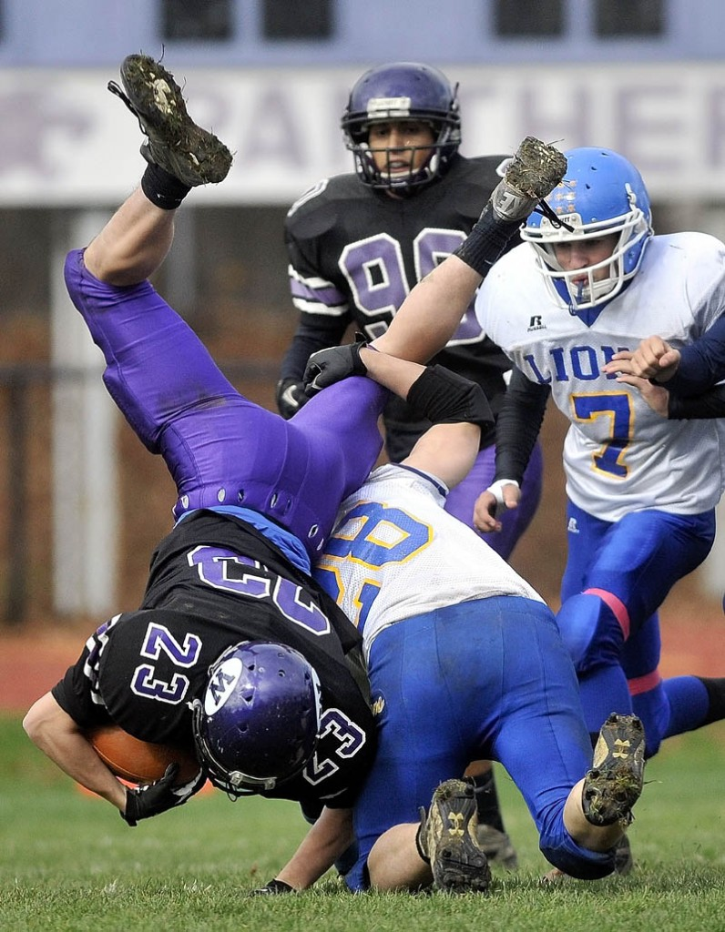 UP AND OVER: Waterville's Jordan DeRosby (23) gets flipped head over heels by Belfast defender Carl Dodge (28) on the opening kickoff during the Panthers' 31-14 win over Belfast in the Pine Tree Conference Class B semifinals Saturday in Waterville.