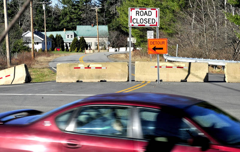 Traffic passes the Whittier Road in Farmington on Wednesday. The road that has been blocked off due to erosion of soil between the roadway and Sandy River.