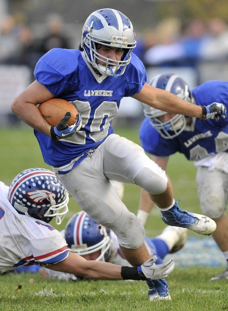 ON THE RUN: Lawrence running back Anthony Sementelli (20) breaks the tackle of Messalonskee defender Jake Dexter, left, in the third quarter of the Bulldogs' 27-0 win in a Pine Tree Conference Class A semifinal Saturday in Fairfield.