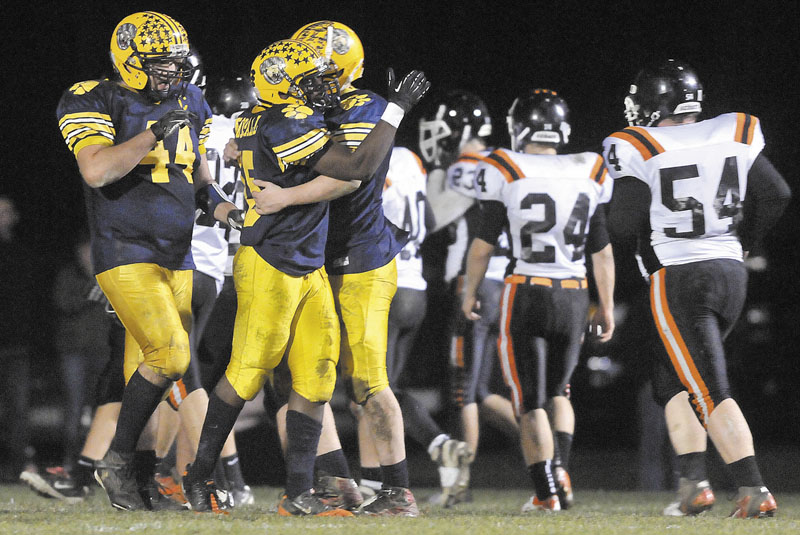Mt Blue High School's Kindle Bonsall, center, celebrates his 24-yard touchdown catch with quarterback Jordan Whitney, right, in the second quarter against Gardiner Area High School on Friday at Kemp Field in Farmington.