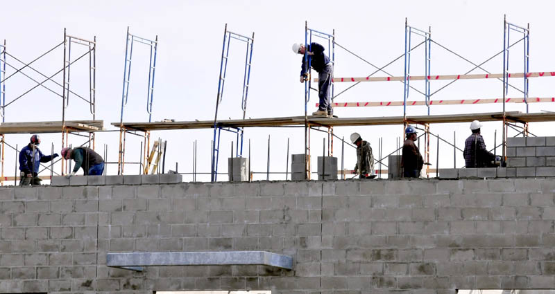 Workers lay cement blocks on the ongoing expansion projects at Mt. Blue High School in Farmington on Wednesday.