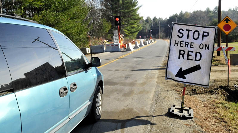 A motorist stops and waits for the signal to proceed along a portion of the Whittier Road in Farmington on Wednesday. The road has been closed due to erosion near the Sandy River, but this week officials reopened one lane to traffic.