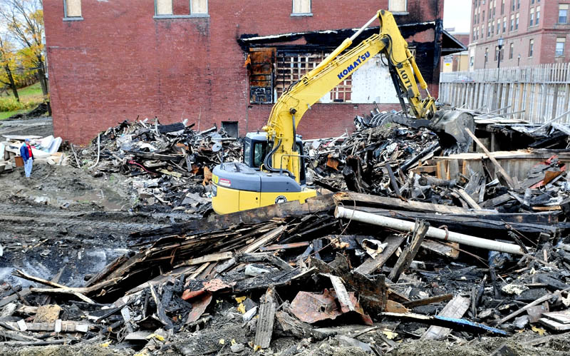 "Property owner Bob Hagopian, left, watches on Thursday as an equipment operator cleans up the burned remains of a former antique store that burned last March on Main Street in Madison. Hagopian plans to rebuild at the site next spring. ""Everyone is excited that I am cleaning this up,"" he said."