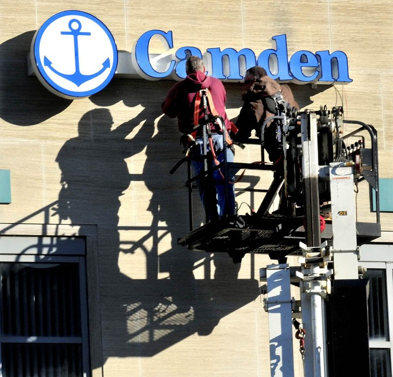 Workers with NeoKraft Signs company install the Camden National Bank sign on the former Bank of America branch on Main Street in Waterville on Tuesday. Bank of America sold its branches in Maine north of Lewiston earlier this year.