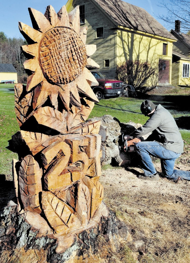 Eric Ogden cuts up sections of a maple tree left over after sculptor Pasco Grove carved the trunk into a large sunflower and street number at Ogden's home in Winslow on Sunday.