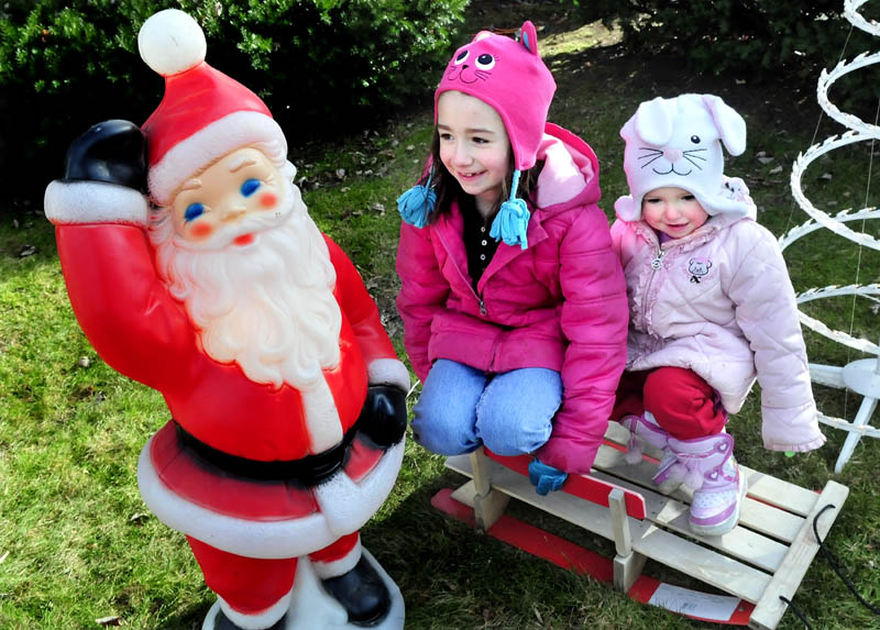 "Skyla Dean, left, and her sister, MacKenzie, play on the Christmas decorations their father was setting up on Main Street in Pittsfield on Sunday. ""I love Santa and Christmas is my favorite,"" Skyla said."