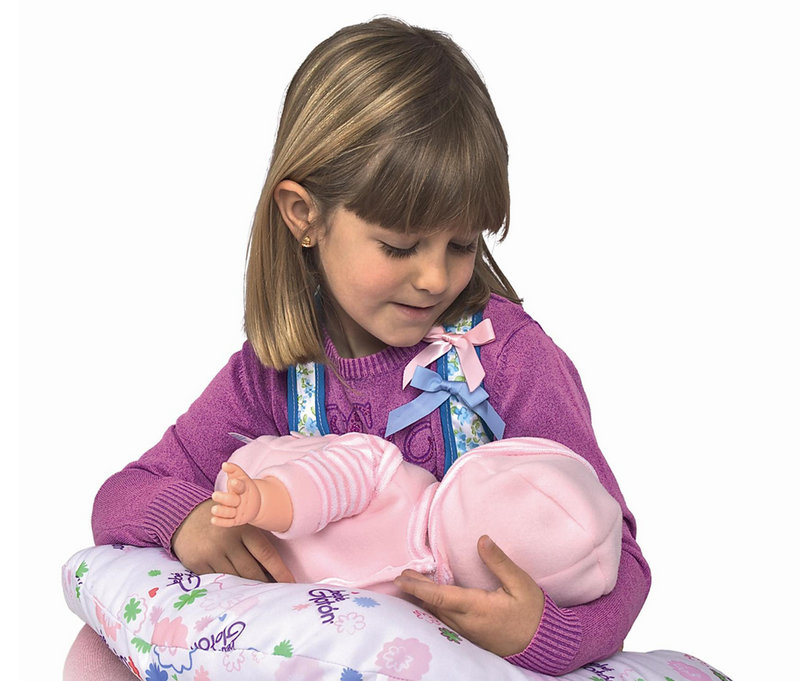 An image from Berjuan Toys shows a girl playing with the Breast Milk Baby doll, which makes suckling sounds when prompted by sensors.