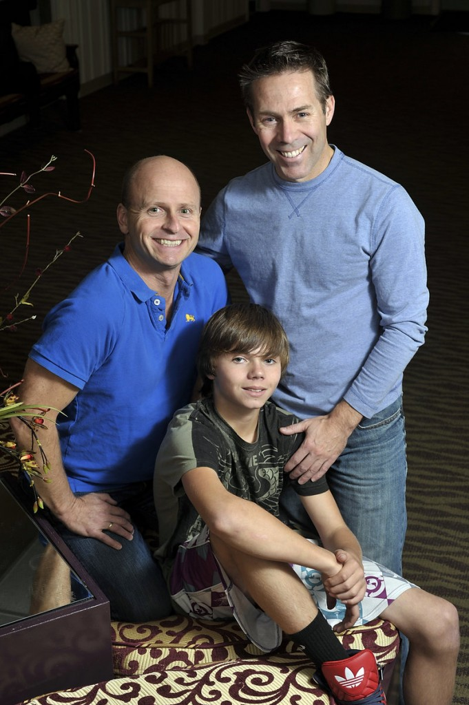 Ray Dumont, left, partner Rodney Mondor, right, and their son, Ethan Mondor, pose for a family portrait at Lyric Theater in South Portland. The men got engaged at Tuesday's Question 1 victory celebration.