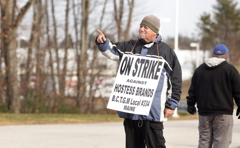 Hernan Descart points to a car carrying two supervisors away from the Hostess plant on Friday. Descart, of South Portland, worked at the plant for eight years.